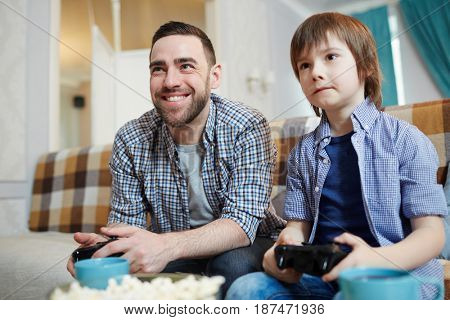 Man and his son with controllers enjoying video-game