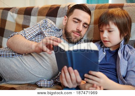 Father and son reading book while relaxing on couch