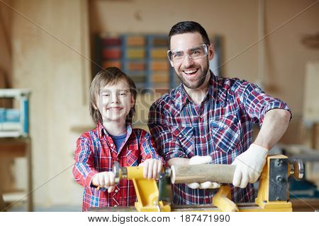 Family of father and son woodworking together