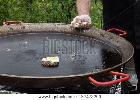 The cook prepares steaks in a huge picnic pan. Outdoors.