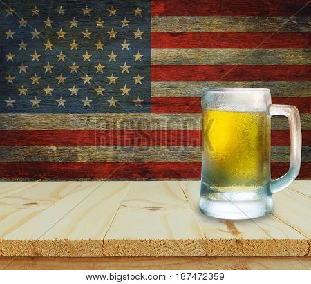 Glass of beer on wooden table. USA flag background celebrate American Independence Day of 4th July