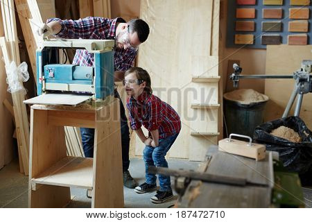 Young man showing his son how to work on planing machine