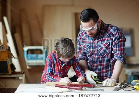 Carpenter and his son working with wooden planks