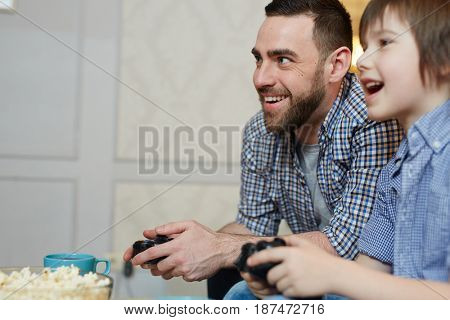 Man and boy with controllers gaming at leisure