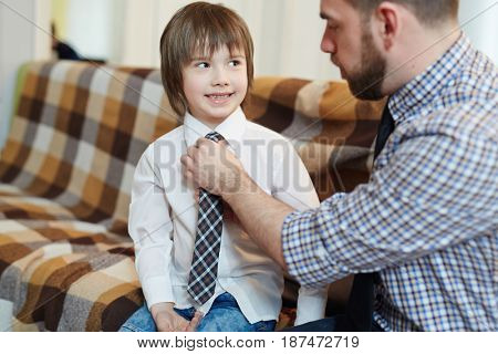 Man helping his son with necktie while getting dressed
