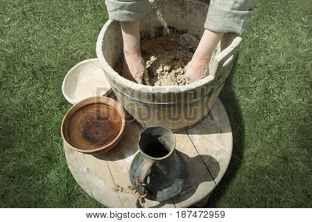 Woman hands preparing dough in medieval ware. Medieval ware: wooden tub and ladle, ceramic pitcher and bowl.