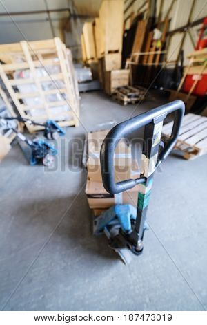 Industrial warehouse. Manual forklift. Focus on top of the handle.