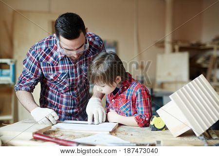 Creative man and boy making starling-house in workshop