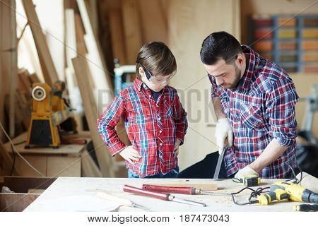 Little boy and his father wood-carving in workshop
