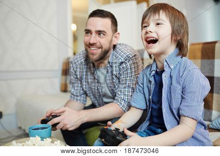Excited boy with joystick gaming with father at home