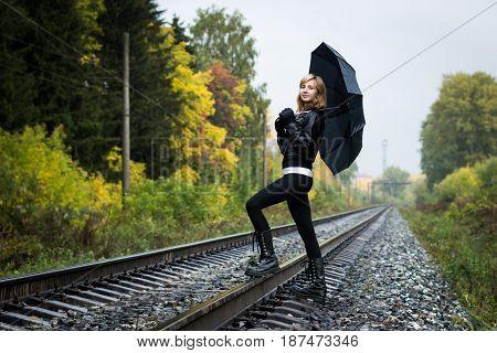 Girl, Umbrella And Rails In Autumn