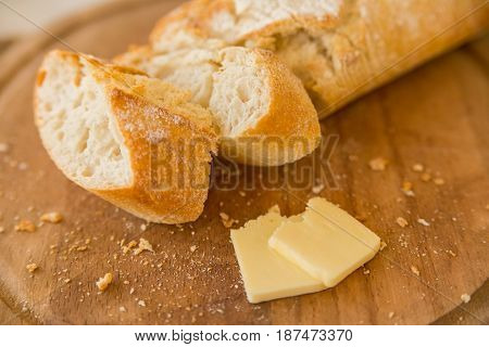 Close up cut fresh french baguette and two slices of cheese on wooden cutting board