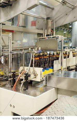 Automatic packaging machine packs bottles of beer in plastic wrap.