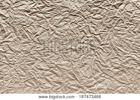 the old crumpled sheet of paper of beige color for the abstract textured background and for wallpaper