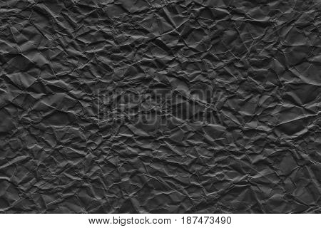 the old crumpled sheet of paper of black color for the abstract textured background and for wallpaper
