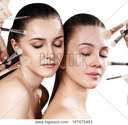 Cosmetics brushes doing make-up to young women. Over white background.