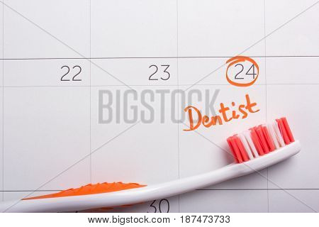A calendar with a marked date for a visit to the dentist. Orange Toothbrush on calendar
