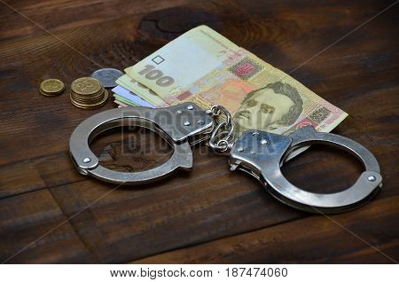 A Photograph Of A Certain Amount Of Ukrainian Money And Police Handcuffs. Concept Of Illegal Earning