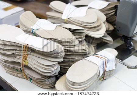 Stacks of leather shoe insoles, blank for shoe production.