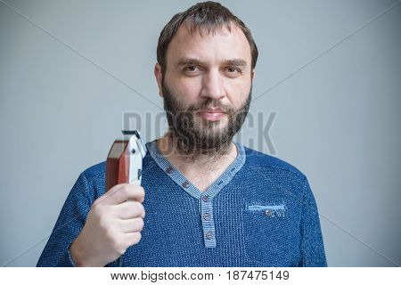 Handsom bearded man in blue sweater holds electric shaver