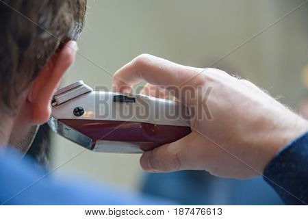 Close up back view of male hand holding electric shaver in front of mirror