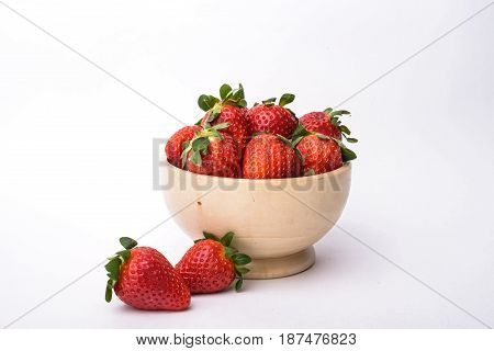 Close up bowl full of fresh strawberries on white background