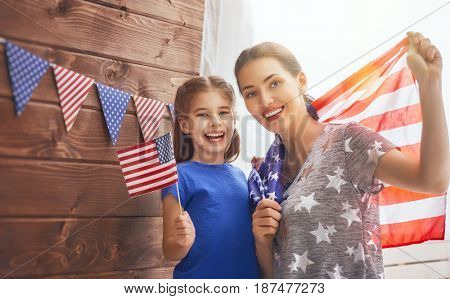 Patriotic holiday. Happy family, mother and her daughter child girl with American flag at home. USA celebrate 4th of July.
