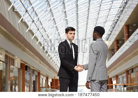 Intercultural businessmen shaking hands after negotiation