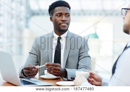 Young manager listening to his employer at meeting