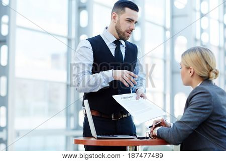 Business leader showing his secretary new contract and explaining its terms