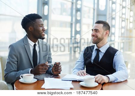 Two anaysts having business talk by cup of coffee