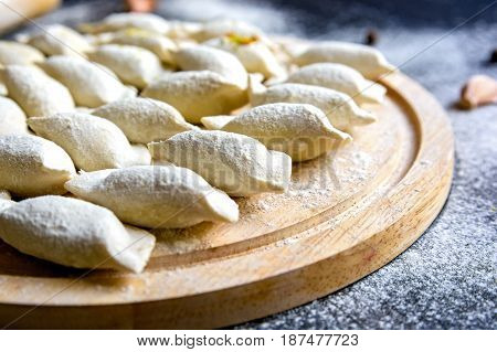 Close up of prepared for cooking variniki on wooden board covered with flour