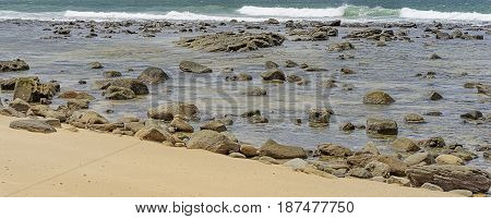 Australian Pacific ocean coastline with sandy beach and rocky shoreline during flood tide panorama view