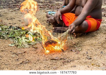 DABANA, SRI LANKA - CIRCA DECEMBER 2016: Vedda men making fire. Veddas are an indigenous people of Sri Lanka living in tribes in the jungle