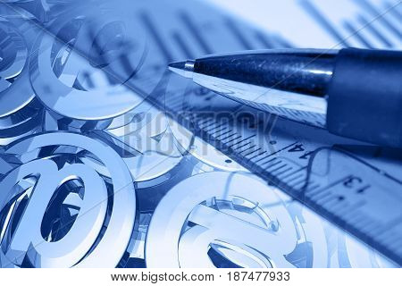 Business background in blues with pen mail signs and ruler.