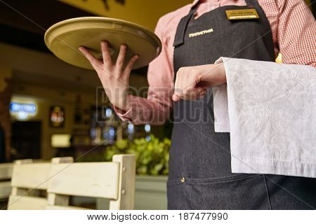Yong waiter in tuxedo and gloves holding empty tray and napkin in restaurant