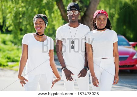 Three Stylish African American Friends, Wear On White Clothes Against Luxury Red Sport Car. Street F