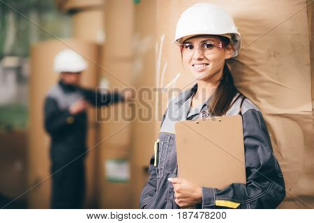 Portrait of a female worker with paper rolls on the background