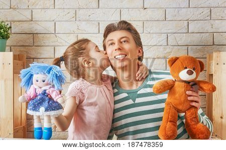 Happy loving family. Father and his daughter in kids room. Funny dad and lovely child having fun and playing performance in the puppet theater indoors. Doll and teddy bear.
