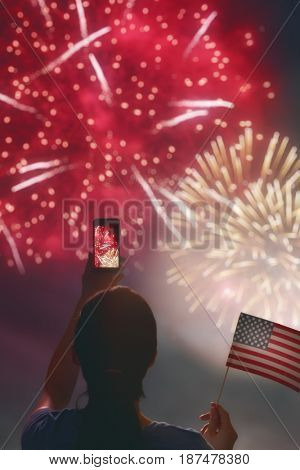 Patriotic holiday. Happy young woman with American flag is looking fireworks. USA celebrate 4th of July.