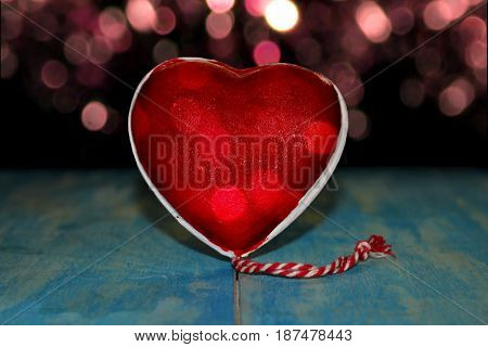 beautiful figurine red heart on blue wooden boards on the background of sparkles