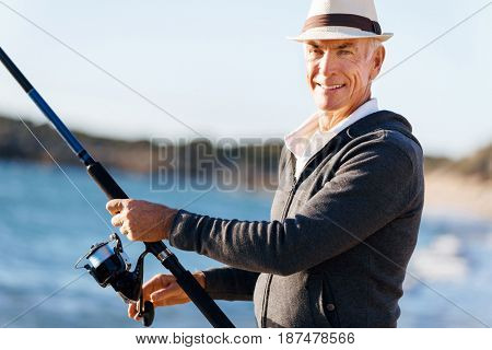Senior man fishing at sea side