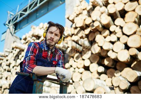 Portrait of man wearing earmuffs looking at camera while working on timber cutting site