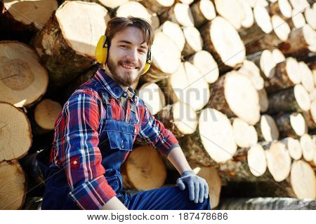 Portrait of man wearing earmuffs looking at camera and smiling while working on timber cutting site, sitting against pile of logs