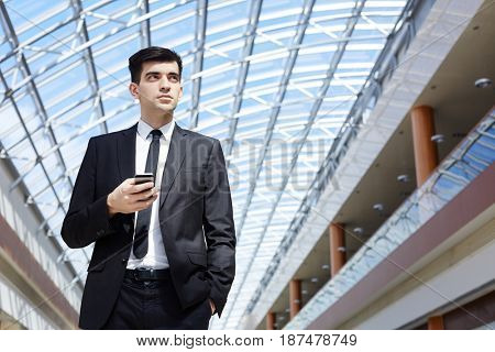 Serious young entrepreneur with smartphone