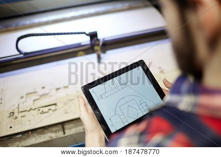 High angle shot of factory worker using digital tablet to operate laser cutting machine in workshop