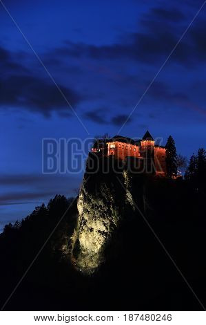 The medieval castle of Bled perched on a cliff above the lake during the night Slovenia.