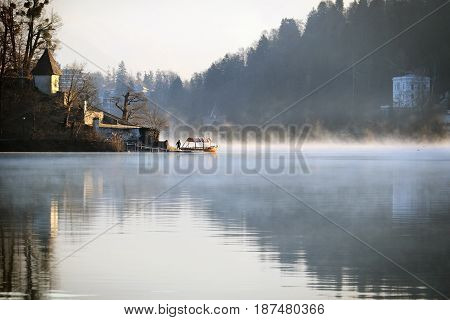 A Pletna boat near the Assumption church in the lake of Bled Slovenia.