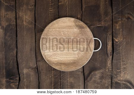 Top View Of Scratched Circular Chopping Board On Wooden Background