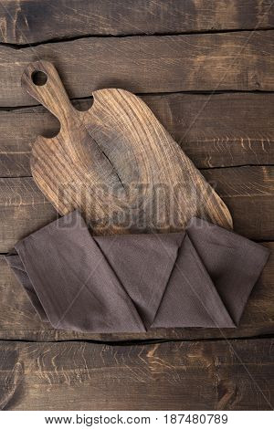 Top View Of Old Scratched Chopping Board With Brown Napkin On The Table
